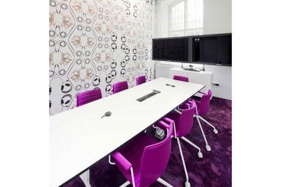 Escritório divertido tem poltronas coloridas na sala de reunião.