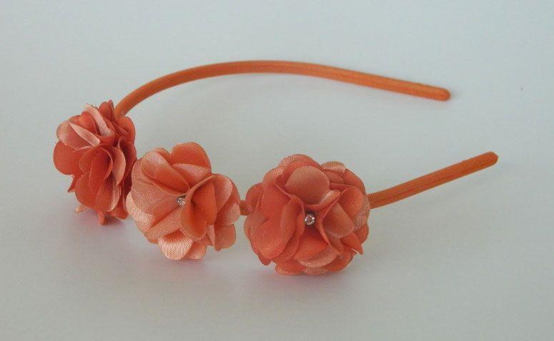 """Tiara com flores por R$ 20,00 na <a href=""""http://www.elo7.com.br/tiara-3-flores-laranja/dp/4D20FA"""" target=""""_blank""""> Elo7</a>"""