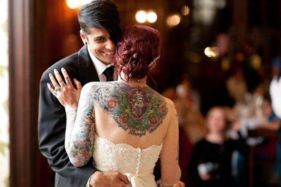 Detalhe da tatuagem nas costas evidenciada pelo recorte do vestido