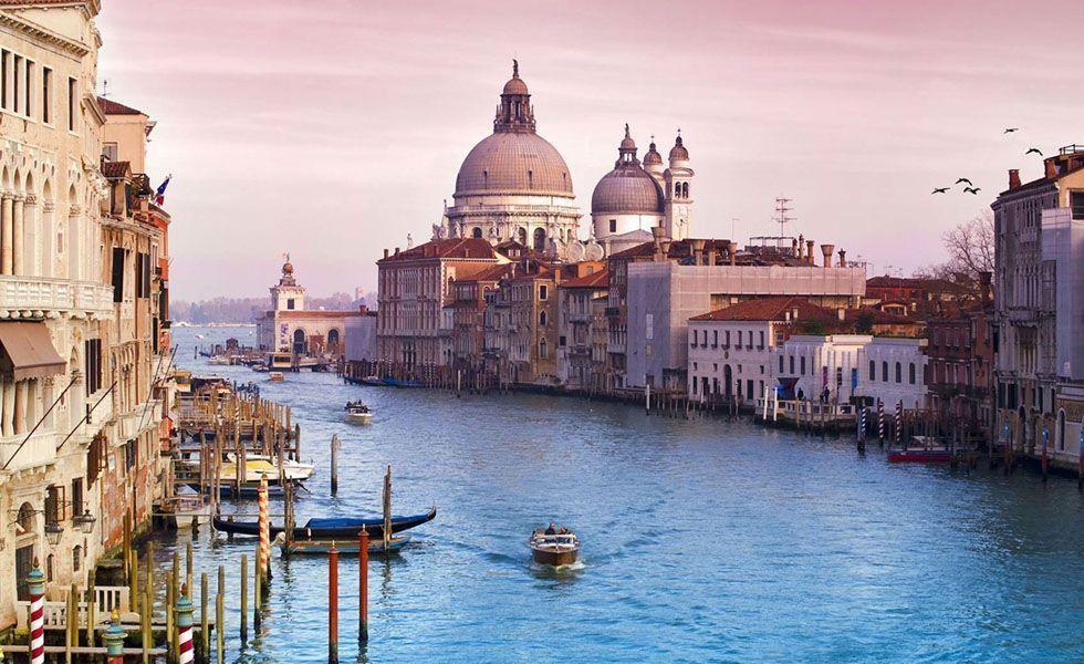 <p>Símbolo vivo do romantismo, <strong>Veneza</strong> – localizada no nordeste da Itália - inspira os sonhos de muitos casais ao redor do mundo. Canais cortados por pontes em arco, gôndolas deslizando pelas águas e palácios medievais formam a identidade desta cidade mística que está na lista de desejo de viagem da maioria das pessoas. </p> <p>A cidade recebe turistas de diversas partes do mundo durante o ano todo. Para desfrutar da beleza dessa cidade é necessário disposição para acordar cedo e andar muito para conhecer cada canto dela. Na Praça de São Marcos - principal ponto turístico da cidade - é onde está localizada a Basílica de São Marcos e a Torre do Relógio. Aproveite para passear e fotografar a praça que é coberta pelos pombos da cidade. Desfrute também de um café da manhã no Caffè Florian, aberto em 1720 - o café mais antigo da cidade. Peça um chocolate quente e aproveite para ler um livro e namorar. Para o almoço conheça o cardápio de comida italiana e a imensa carta de vinhos do Le Bistro de Veneze. O ambiente romântico do restaurante Antico Martini é ideal para um jantar a dois. </p> <p>Veneza também é um excelente lugar para compras. Visite o Annick Goutal, ótimo lugar para comprar perfumes e não deixe de conhecer a Bottega Veneta, onde estão localizadas as principais grifes italianas.</p>