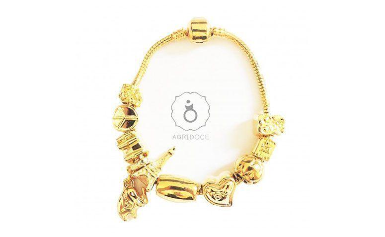 """Pulseira com os berloques em metal dourado por R$79,90 na <a href=""""http://www.agridocefashion.com.br/berloques/pulseira-berloques-pandora-inspired-dourada.html#!prettyPhoto"""" target=""""blank_"""">Agridoce Fashion</a>"""