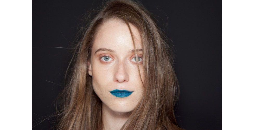 """<p>A beleza da Triton foi assinada por Robert Estevão e trouxe um look simples e despojado. A maquiagem foi a famosa <a href=""""http://www.dicasdemulher.com.br/maquiagem-nude/"""">""""make nada""""</a> que teve como único destaque as bocas em tons inusitados como o azul, verde, marrom, fúcsia e preto. </p> <p>Os cabelos estavam soltos e foram escovados para ficar com uma textura """"podrinha"""". </p>"""