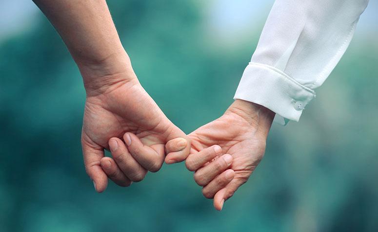 Casal de mãos dadas, simbolizando uma promessa