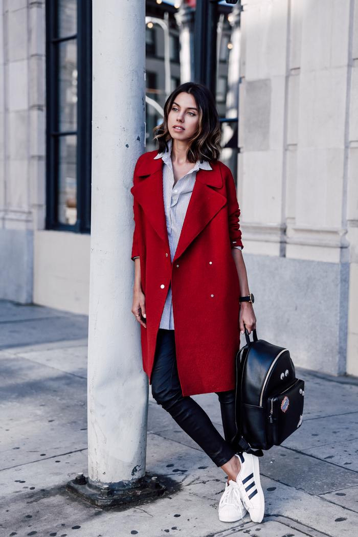 Look sobretudo vermelho, camisa listrada, legging de couro e tênis Adidas