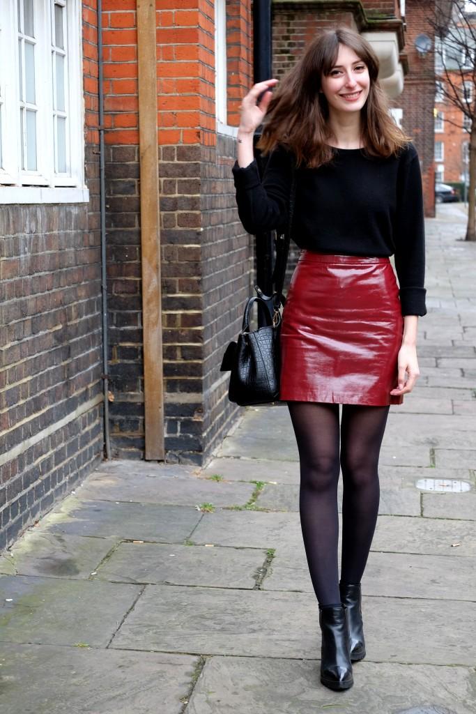 Look saia de vinil vermelha, suéter, meia-calça e bota de cano curto preta
