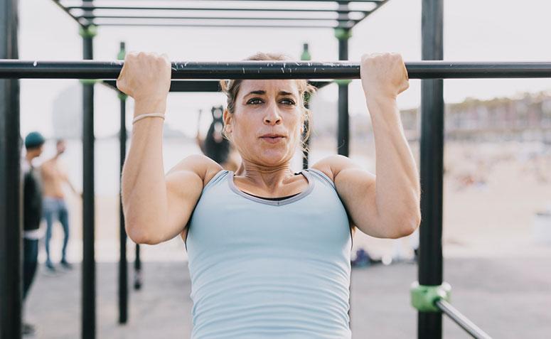 Mulher se exercitando em barra fixa