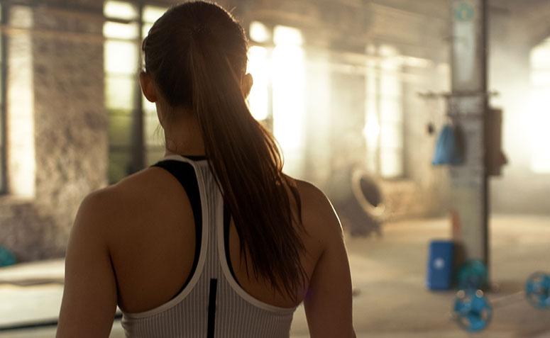 mulher de costas olhando para a academia