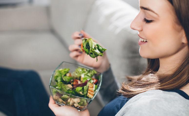 mulher degustando um prato de salada