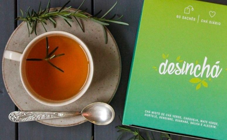 Xícara de chá ao lado de embalagem do Desinchá